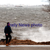 JIM VAIKNORAS/Staff photo A man walks with a camera as the Merrimack River splashes into Water Street in Newburyport.