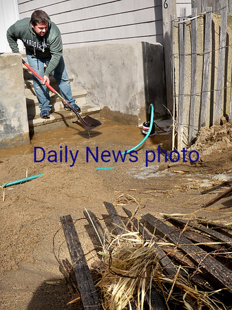 BRYAN EATON/Staff photo. Jamie Emard of Smith Properties, a management company in Merrimac, uses a shovel to create water flow and a submersible pump to drain the bottom floor of one of their properties on North End Boulevard in Salisbury Beach on Monday afternoon.