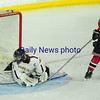 JIM VAIKNORAS/Staff photo  Newburyport's Ken Hodge with a leg save on Winchester's Ryan McCarthy at the Tsongas Center in Lowell Thursday night.