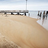 BRYAN EATON/Staff photo. Sand that has accumulated at Captain's Fishing Parties and Cruises' pier is to be used to created a berm near Reservation Terrance on Plum Island, the area of which has eroded during March storms.