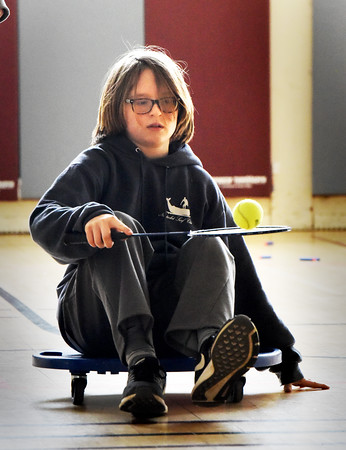 BRYAN EATON/Staff photo. Jack Sherman, 12, moves along on a scooter while balancing a tennis ball on a tennis racquet on Tuesday afternoon. He was in the gymnasium at the Newburyport Rec Center at the Brown School competing in a relay contest.