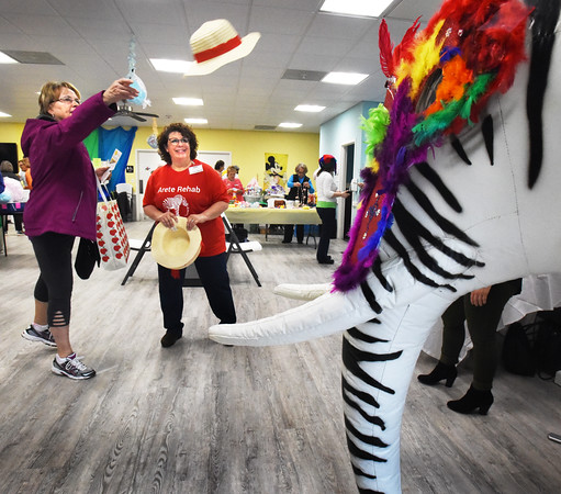 BRYAN EATON/Staff photo. Anne Brennan of Seabrook tries the hat on giant zebra-colored elephant as Janet Mahoney of Arete Rehab in Amesbury looks on. They were at a health fair at the Hilton Senior Center in Salisbury that was billed as a Winter Carnival, a fun filled afternoon with activities, games, food and a chance to learn about local senior supporting organizations.