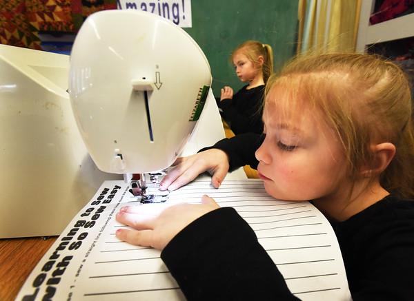 BRYAN EATON/Staff photo. Sophie Simard, 6, right, and her twin sister Brooklyn practice sewing on straight lines as they learn the basics before going on to make small, then larger, pillows. They were in Judy Gaffney's sewing class at the Boys and Girls Club in Salisbury where she's letting younger children learn the craft.