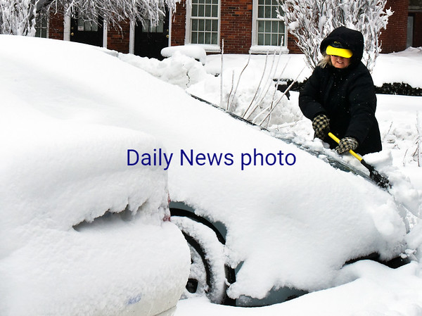 BRYAN EATON/Staff photo. Fran Gibbons cleans her car off in the Green Street Parking Lot in Newburyport early Thursday morning.