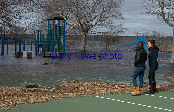 JIM VAIKNORAS/Staff photo Bailey Gardelia and Sophia Dixon, both from Rowley check out the flodding at Cashman Park in Newburyport Saturday.