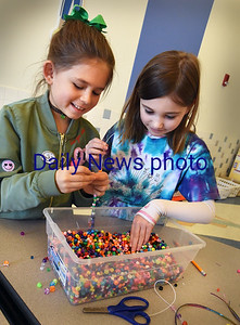 BRYAN EATON/Staff photo. While some youngsters were outside the Bresnahan School in Newburyport pursuing snow activities, some stayed in the cafeteria doing crafts in the YWCA Afterschool Program. Sadie Aiello, left, and Quinn Fenn, both 8, chose colorful beads to make their own bracelets.