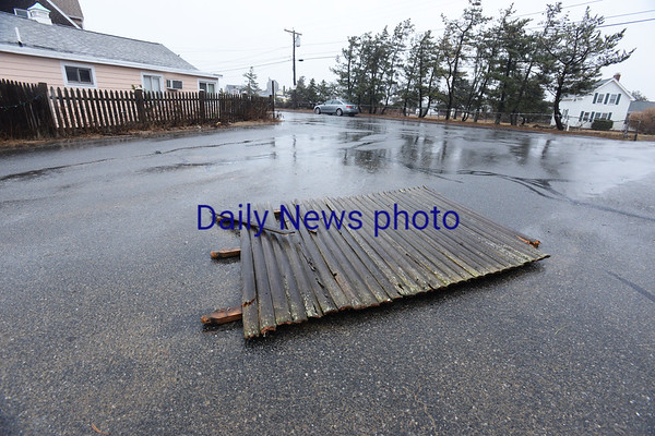 BRYAN EATON/Staff photo. A section of fence blew and landed to the entrance of the parking lot at Plum Island Point.