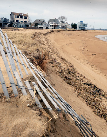 BRYAN EATON/Staff photo. Recent nor'easters have scoured the sand from the dunes on Plum Island making these homes at Reservation Terrance, north of 73rd Street, vulnerable. A plan is to take sand from around the pier at Plum Island Point to create a berm.