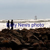 JIM VAIKNORAS/Staff photo A couple walk among the debris and high surf at the North Jetti at Salisbury Beach Reservation