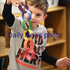 BRYAN EATON/Staff photo. Dylan Silva, 5, holds up a paper chain to show his kindergarten teacher Jane Keeler at Salisbury Elementary School. The youngsters made the colored chains as they learned about primary colors and colors of the rainbow along with motor skills.