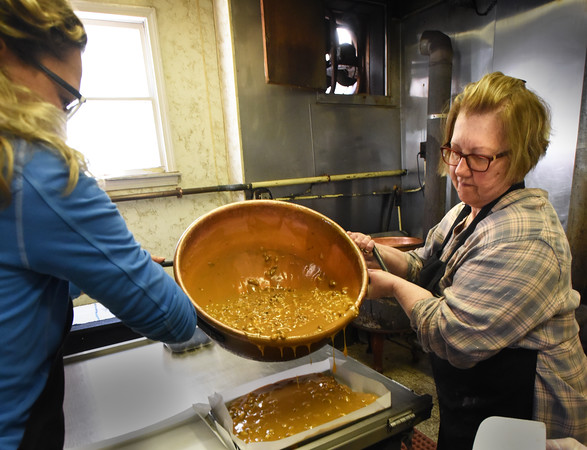 BRYAN EATON/Staff photo. Fritz, left, and Debbie Powers, who has worked at the shop for 12 year, pour fudge into lined tins.