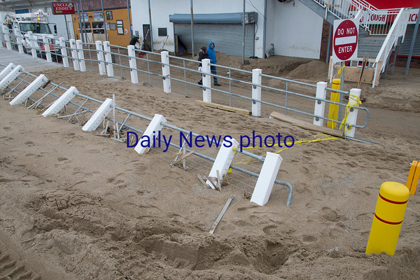 JIM VAIKNORAS/Staff photo The railing at new board walk at Salisbury Beach Center is bend and half buried in sand from the weekends storm.