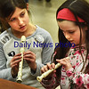 BRYAN EATON/Staff photo. BRYAN EATON/Staff photo. Samantha Evans, left, and Lillian Fulmer, both 8. try to get the hang of positioning their fingers over holes in recorders at Amesbury Elementary School. They were working on their music literacy and learning how to read notes in Alicia Harlov's music class.