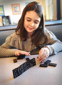 BRYAN EATON/Staff photo. Olivia Bertolami, 8, creats a mini Great Wall of China using dominoes at the Bresnahan School in the YWCA Afterschool Program on Monday afternoon. The youngster was quite knowledgable about the wall saying she learned about it in the STEM class at the school.