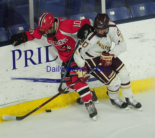 JIM VAIKNORAS/Staff photo  Newburyport's Jacob Grossi-Hoggfights for the puck with Winchester's Robert Falso at the Tsongas Center in Lowell Thursday night.