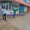 JIM VAIKNORAS/Staff photo Jacob Prunier of Hampton and Matt Mason of Merrimac shovel sand thrown up by this weekends storm at Joe's Playland at Salisbury Beach center.