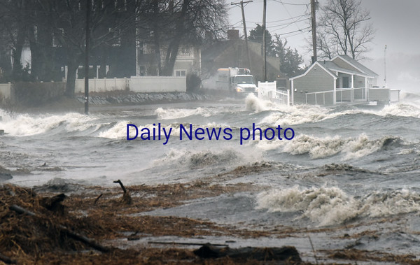 BRYAN EATON/Staff photo. Water from the Merrimack River spills onto Water Street in Newburyport which was blocked to traffic.