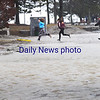 BRYAN EATON/Staff photo. Youngsters run through the NRA West Parking lot in Newburyport flooded the the overflowing Merrimack River in Newburyport.