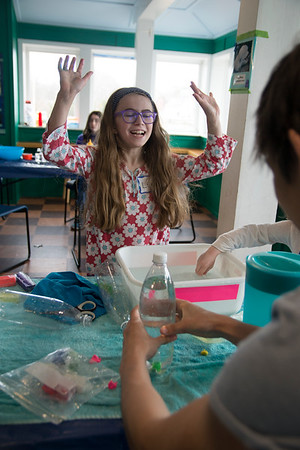 JIM VAIKNORAS/Staff photo Lexi Dorow, 8, of Danville, celebrates establishing buoyancy during an experiment run by volunteer Seba Gonzales at the 12th Annual Celebrate the Seas Free-for-All at the Joppa Education Center in Newburyport Sunday.