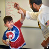 BRYAN EATON/Staff photo. Cy Alphonse works with Reed McKnight, 7, on some defensive moves. The youngsters are in the fourth week of the class and will be breaking slats of wood as they progress.