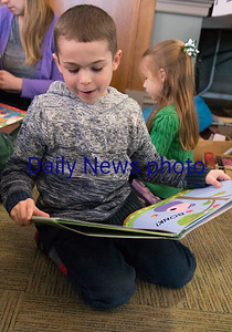 JIM VAIKNORAS/Staff photo Jimmy Manning, 6, reads Peppa Pig, one of a stack of books he bought Friday at the Annual Newburyport Library Book Sale.