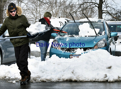BRYAN EATON/Staff photo. Jenny Putnam cleans off her car as son, Jamie, 13, moves snow as cleanup from Tuesday's storm continues. The residents, who live nearby, were parked in Newburyport's Green Street Parking Lot for the snow emergency.