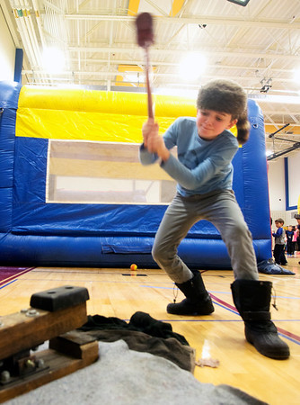 """JIM VAIKNORAS/Staff photo Lucas Itrato, 9, swings a hammer to ring the bell in a feat of strength at the Friends of Newburyport Youth Services """"Hello Spring"""" celebration at the Bresnahan School in Newburyport Saturday. The event also included more than 500 cupcakes for sale, music, carnival games, music, and a cupcake bake-off."""