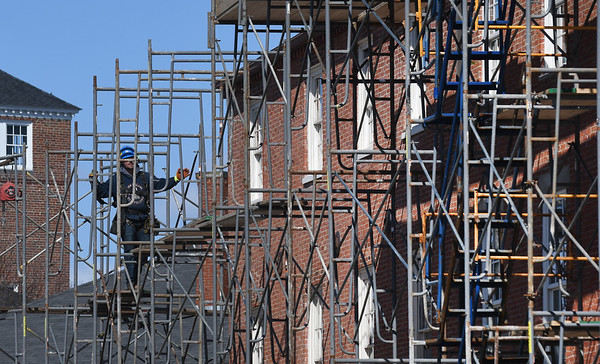 JIM VAIKNORAS/Staff photo Workers put up scaffolding around the East Row at the corner of Liberty and State Street in Newburyport Tuesday. The roof is being replaced.