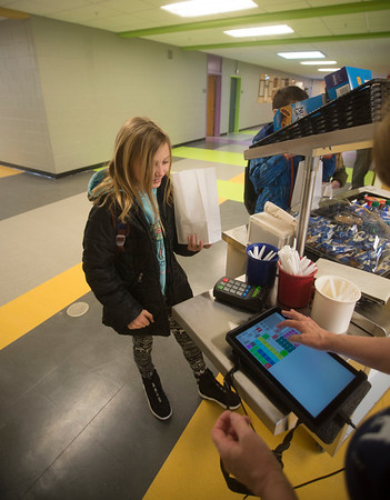JIM VAIKNORAS/Staff photo Lyla Harris, 9, pays for her food at the breakfast cart at the Molin School in Newburyport.