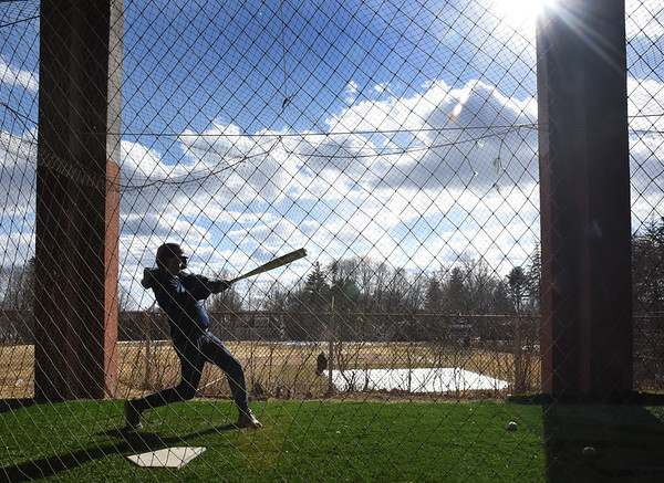 BRYAN EATON/Staff photo. Spring started at 5:58 p.m. on Wednesday and this week started high school spring sports practice under sunny skies. Jack Fehler practices in the batting cage under World War Memorial Stadium stands at Newburyport High School. More photos in the sports section.