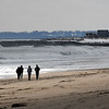 JIM VAIKNORAS/Staff photo A small group of people walk along a wind swept beach in Salisbury Monday afternoon.