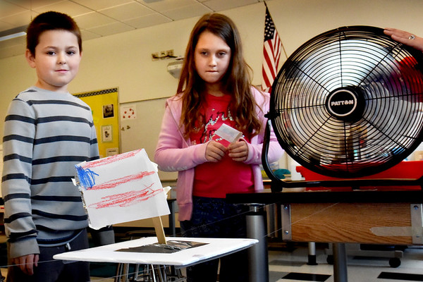 BRYAN EATON/Staff photo. DJ Ellison, 7, left, and Daria Lucentestabile, 6, look on as a fan blows his sail along fishing wire at the Bresnahan School on Thursday afternoon. The students in Kristin Spinney's STEM (Science, Technology, Engineering and Mathematics) class were studying mechanical engineering to learn about wind-powered machines.