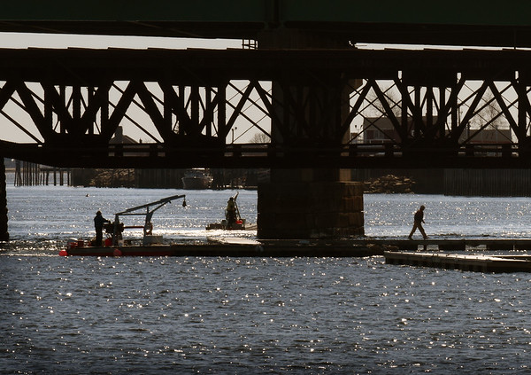 BRYAN EATON/Staff Photo. Crew from Newburyport Harbor Marina install docks on the Merrimack River behind River's Edge Condominiums on Thursday morning, a sign that boating season is not far away.