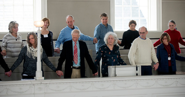 JIM VAIKNORAS/Staff photo  Parishioners hold hands during a Laying on of Hands ceremony at the installation of Rebecca Michaela Bryan as the 16th settled minister of the First Religious Unitarian Universalist Church in Newburyport Sunday.