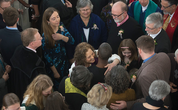 JIM VAIKNORAS/Staff photo Reverend Rebecca Michaela Bryan hugs her parishioners during a Laying on of Hands ceremony at her installation as the 16th settled minister of the First Religious Unitarian Universalist Church in Newburyport Sunday.