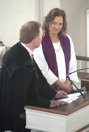 JIM VAIKNORAS/Staff photo Reverend Rebecca Michaela Bryan looks on as Reverend John Gibbons gives the Charge to the Minister at her installation as the 16th settled minister of the First Religious Unitarian Universalist Church in Newburyport Sunday.