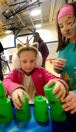 "JIM VAIKNORAS/Staff photo Harper Kulowiec, 6, and Emma Botto-Hanson stack cups at the Friends of Newburyport Youth Services ""Hello Spring"" celebration at the Bresnahan School in Newburyport Saturday. The event also included more than 500 cupcakes for sale, music, carnival games, music, and a cupcake bake-off."