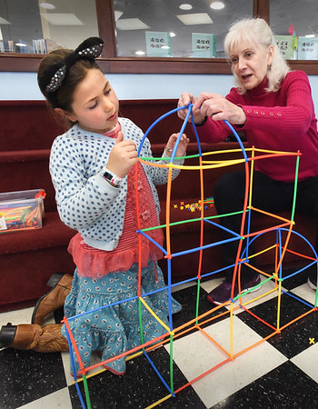 """BRYAN EATON/Staff photo. Clover Eichler, 7, gets help from her grandmother Ellen Tirone of Newburyport as she constructs a building made of straws during STEM Structures in the Children's Room at the Newburyport Public Library on Tuesday afternoon. Clover is visiting from San Francisco, where there's school vacation, for her """"birthday week"""" though she doesn't turn eight for a couple weeks."""