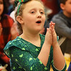 BRYAN EATON/Staff photo. Wearing Irish garb, Kate Devlin, 7, claps at stepdancers performing at the Bresnahan School in Newburyport on Friday morning. Dancers from three schools: Bracken School of Irish Dance; Murray Academy and Heavey Quinn Academy of Irish Dance performed before early release.