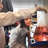 BRYAN EATON/Staff photo. Isaac Boehl, 6, holds a hand over a beaker filled with colored water, dry ice and a magnet which causes the liquid to replicate the spinning of a tornado showing Claire Richards, 7, what his science experiment is about. They were at the STEM Fair at Amesbury High School sponsored the the PTO on Saturday.