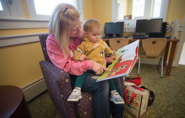 JIM VAIKNORAS/Staff photo Evelyn Younghans, 18 month, and her nanny Elizabeth Owen read Clifford the Big Red Dog at the Salisbury Library Thursday afternoon. They were there for story time and decided to hang around and do some extra reading.