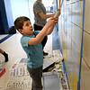 BRYAN EATON/Staff photo. Max Romano, 5, whose mother Julie works at Triton, lent a hand to the cause helping to paint.