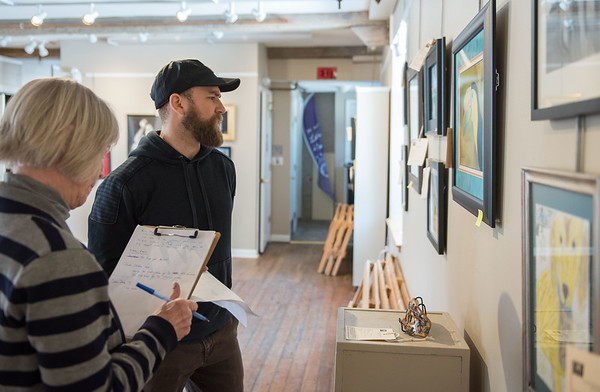 AMANDA SABGA/Staff photo<br /> <br /> Local artist and Youth Services program supervisor Lee Gordon, of Newburyport, judges artwork at the Young and Budding Artist Exhibition at the Newburyport Art Association. Susan Spellman takes notes on his critiques. <br /> <br /> 3/5/19