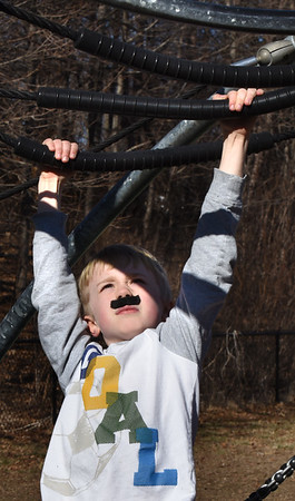 """BRYAN EATON/Staff photo. The nice weather brought the children from the Newburyport YWCA Afterschool Program outside to the Bresnahan School playground yesterday. Colin Farmer, 7, moves along the monkey bars with a """"caterpillar"""" on his lip as it was Moustache Monday."""