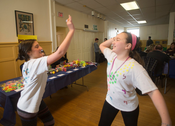 JIM VAIKNORAS/Staff photo Eliza Naftuly, 12, and Ilona Linn, 11, high-five after winning a dart game at a Purim Celebration at the Congregation Ahavas Achim in Newburyport Sunday morning. The celebration included games and prizes, crafts, face painting and a costume contest.