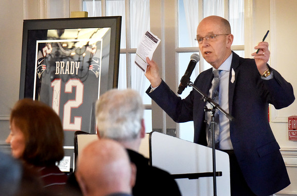 BRYAN EATON/Staff photo. White Ribbon committee member Peter Hoyt presented his Power of One talk then asked for attendees to donate to the cause. Chairman Richard Bazirgan then auctioned off this Tom Brady shirt.