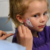 "JIM VAIKNORAS/Staff photo Evelyn Knapp, 6, has a unicorn painted on her face by Katie Mead at the Friends of Newburyport Youth Services ""Hello Spring"" celebration at the Bresnahan School in Newburyport Saturday. The event also included more than 500 cupcakes for sale, music, carnival games, music, and a cupcake bake-off."
