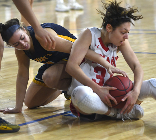 JIM VAIKNORAS/Staff photo Amesbury's Gabriella Redford fights for a loose ball with St.Mary's Pamela Gonzalez in the D3 North final at the Tsongas Center in Lowell Saturday. St. Mary's won the game 59-48.