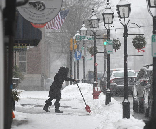 JIM VAIKNORAS/Staff photo Gina Bressler, manager of the Black Dog, clears the snow from the front of her State Street store in Newburyport Saturday morning after the first round of this weekends snow.