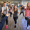 BRYAN EATON/Staff photo. Nock Middle School seventh-graders do some stretching before going into yoga and meditation, from left, Shannon Brock, Gianna Minichiello, Gabrielle Perrin, Lexi Klapes and Michelle Kilroy, all 13. Starting the class in October to relieve stress are classmates, backs to camera, Zoey Calitri, 12, left, and Michelle Seznec, 13, right.